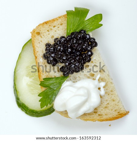 Sandwiches of white bread with fresh cucumber, cream,  black caviar and herbs - stock photo