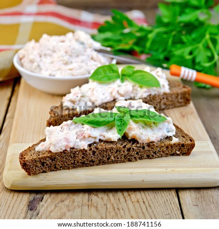 Sandwiches on two pieces of rye bread with cream of salmon and mayonnaise, basil, napkin, parsley on a wooden boards background - stock photo