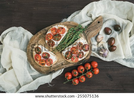 Sandwiches or brushettas with roasted cherry tomatoes, soft cheese, garlic and herbs on a rustic wooden board and white kitchen towel over a dark wood background. Top view - stock photo