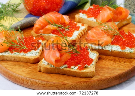 Sandwiches with a salty salmon and red caviar on a wooden board - stock photo