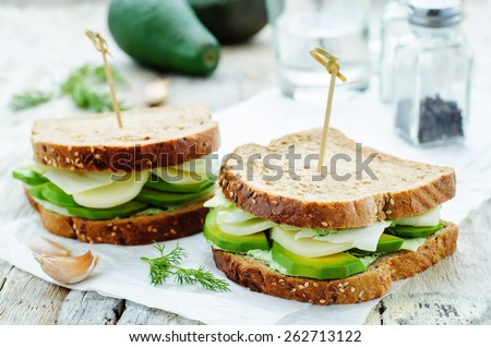 sandwiches with avocado, cheese, cabbage and cheese and herb topping. tinting. selective focus - stock photo