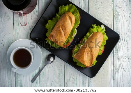 Sandwiches with baguette, ham, vegetable slices and lettuce on black plate, cup of tea and teapot on wooden table. Fast food - stock photo