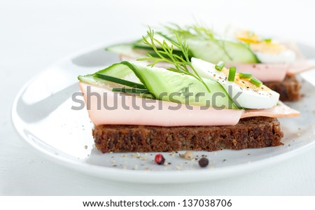 Sandwiches with egg, ham, cucumber and chives on white plate - stock photo