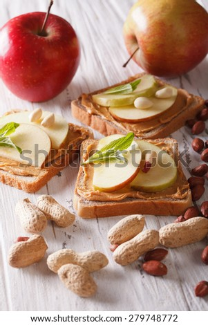 sandwiches with fresh apple and peanut butter on the table. vertical  - stock photo