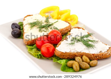 Sandwiches with fresh vegetables, olives, butter and cheese on plate. - stock photo