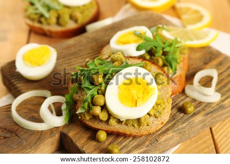 Sandwiches with green peas paste and boiled egg on cutting board with napkin on wooden planks background - stock photo