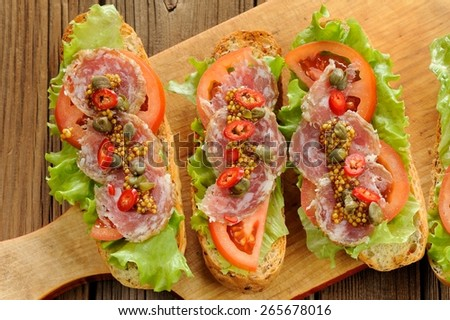 Sandwiches with ham, salad leaves, chili, tomatoes, capers, french mustard on wooden background - stock photo