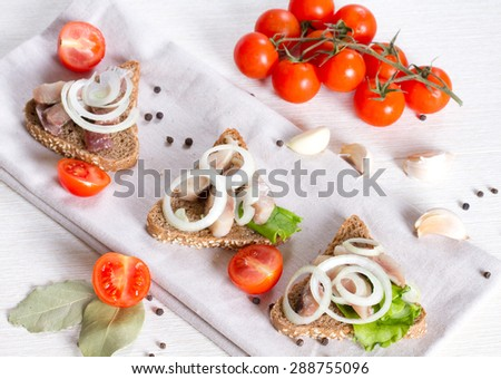 Sandwiches with herring on a napkin and a branch of cherry tomatoes