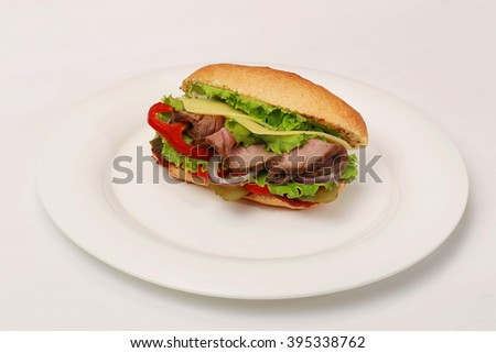 Sandwiches with lettuce, slices of fresh tomatoes, cucumber, ham, salami and cheese. On a white plate. - stock photo
