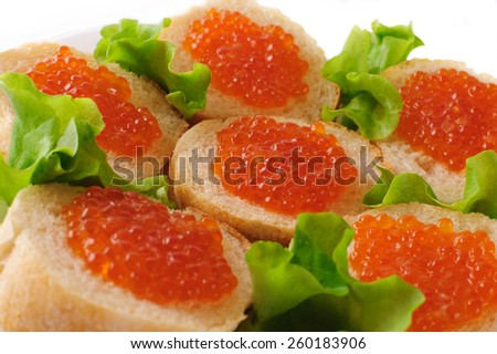 Sandwiches with red caviar and green lettuce. - stock photo