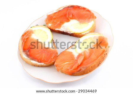 sandwiches with red fish on a white dish