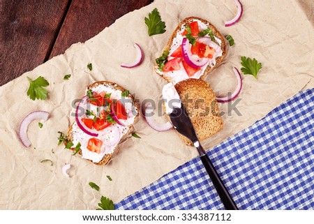 Sandwiches with ricotta pasta, tomatoes and herbs. Bread with ricotta pasta on the table. Bruschetta. Tasty appetizer. Knife, bread, red onion and tomatoes. Checkered tablecloth, paper,  wooden table. - stock photo