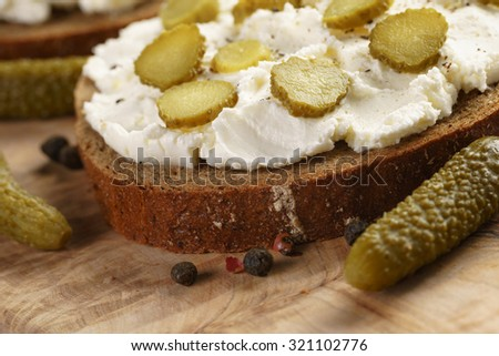 sandwiches with rye bread, cream cheese and marinated cucumbers, rustic food - stock photo