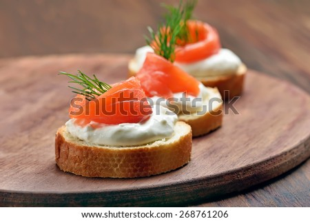 Sandwiches with salmon and dill on wooden cutting board - stock photo