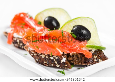 Sandwiches with salmon, olives and lime on a white plate