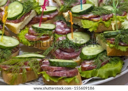 sandwiches with sausage and greens on a platter