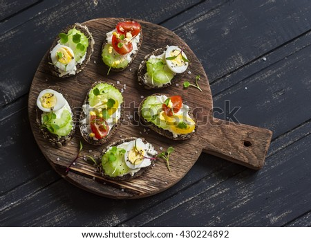Sandwiches with soft cheese, quail eggs, cherry tomatoes and celery. Delicious healthy snack or Breakfast. On a wooden rustic board - stock photo