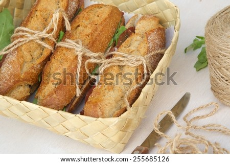 Sandwiches with whole grain bread, rucola,parmesan cheese and bresaola in a woven box. Free space for a text. - stock photo