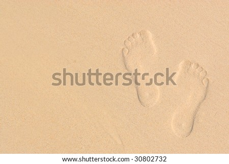 Sandy background with footprints on the beach : summer vacation concept - stock photo