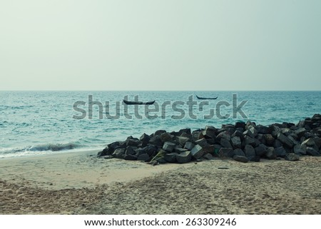 Sandy beach and boat in the sea - stock photo