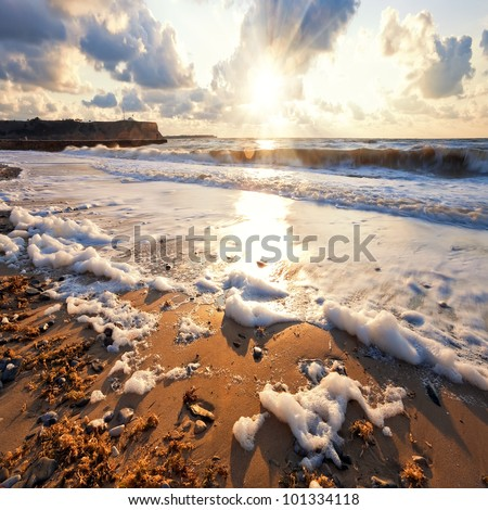 Sandy beach at sunset. Stormy sea