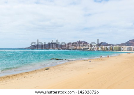sandy beach, blue ocean, the sky in the clouds and cape, stretching into the ocean - stock photo