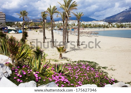 Sandy beach in resort town of Puerto Banus (near Marbella) on scenic Costa del Sol, Andalusia, Spain. - stock photo