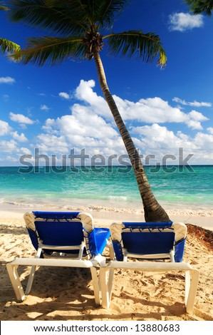 Sandy beach of tropical resort with palm trees and two reclining chairs