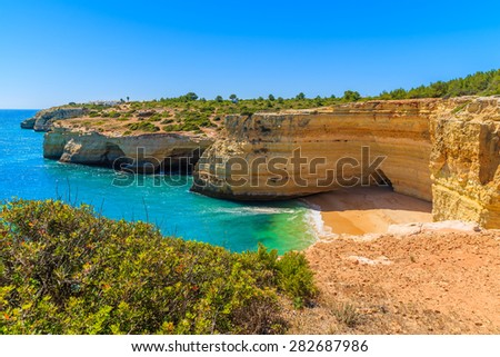 Sandy beach with cliff rocks in small cove near Carvoeiro town, Algarve region, Portugal - stock photo