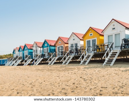 Sandy beach with colorful beach cabanas with white stairs in a row. - stock photo