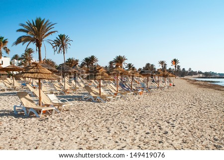Sandy beach with deckchairs and parasols at sunset - stock photo