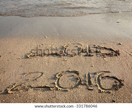 Sandy beach with hand drawn 2015 almost gone by waves and clear 2016