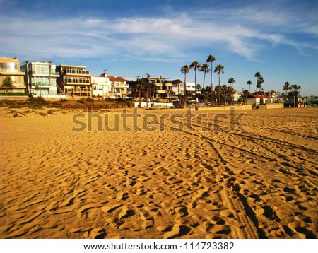 Sandy beach with palm trees and large vacation homes at sunset - stock photo