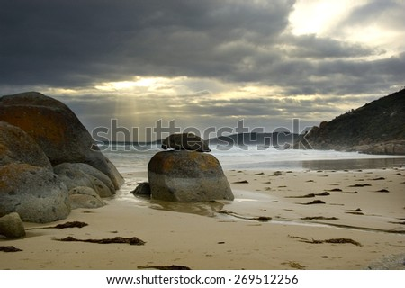 Sandy beach with rocks and dramatic sun ray peaking through the cloudy sky. - stock photo