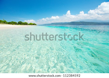 Sandy coast of a wild beach and clear sea of the Bali Barat National Park - stock photo