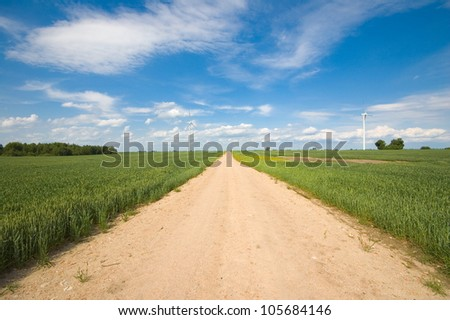 Sandy country road through the fields - stock photo