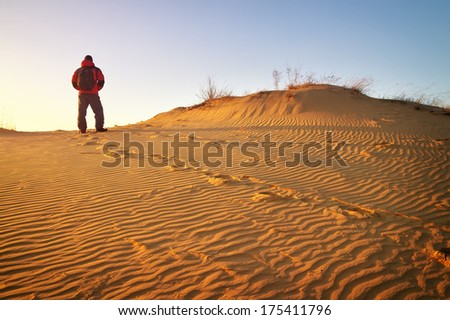 Sandy desert and man in winter clothes standing at a dune top  - stock photo