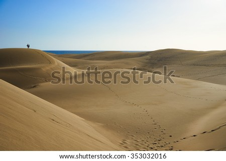 Sandy dunes of a great desert with people / people on huge dune of a desert next to a beach under blue sky with sea in the background and a valley / Large sandy dunes of southbeach in gran canaria