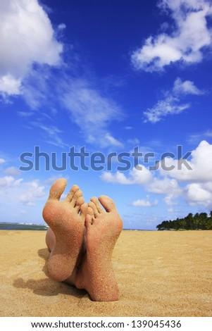 Sandy feet on a tropical beach - stock photo