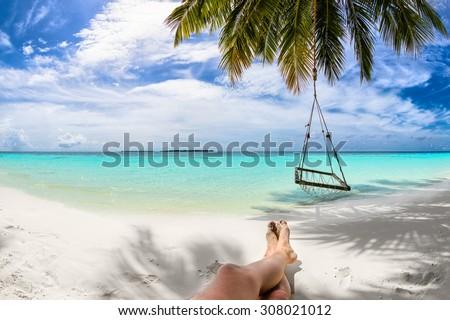 sandy feet on the beach under coco palm - stock photo