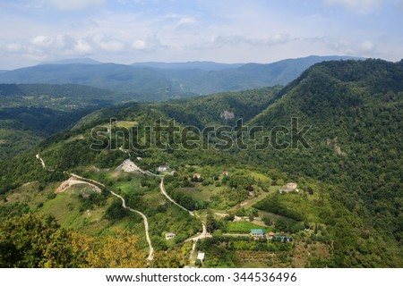 sandy road and small old village houses in caucasus mountains covered with forest in Abkhazia Georgia - stock photo