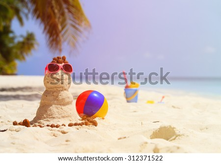 Sandy snowman and toys at sand tropical beach - stock photo