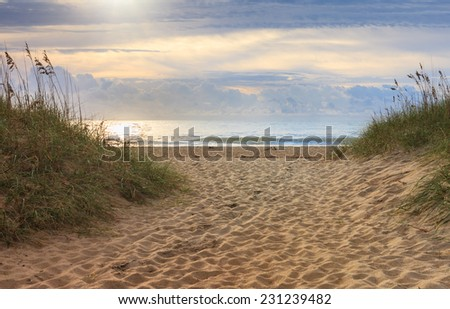 Sandy walkway through the dunes and sea oats to the beach and ocean on the Cape Hatteras National Seashore in North Carolina. - stock photo