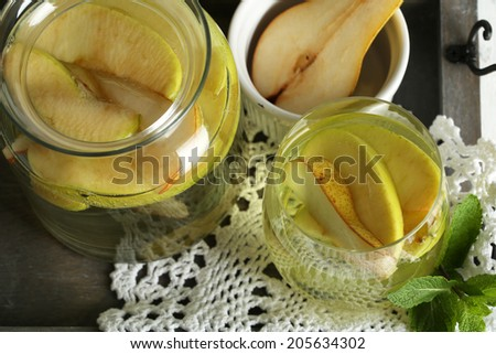 Sangria drink in glass and jar on wooden background - stock photo