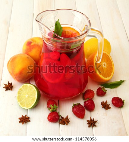 sangria in jar with fruits, on white wooden table