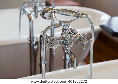 sanitary, plumbing and washing concept - close up of bath tap and shower at bathroom - stock photo