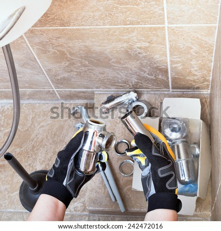 Sanitary technician repairs plumbing trap from sink in bathroom - stock photo