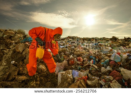 Sanitation worker processing  waste material (sorting, treatment, recycling) on the landfill. - stock photo