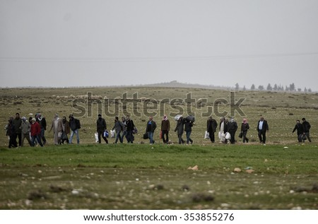 SANLIURFA,TURKEY, 18 FEBRUARY 2015 Syrian refugees walking on Turkey-Syria border in Suruc district.  - stock photo
