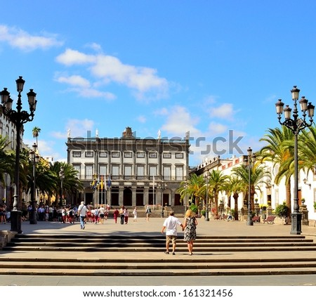 Santa Ana square with many visitors and old town hall in background, historical center of Las Palmas de Gran Canaria with tourists walking a splendid sunny day with radiant blue sky and some clouds - stock photo